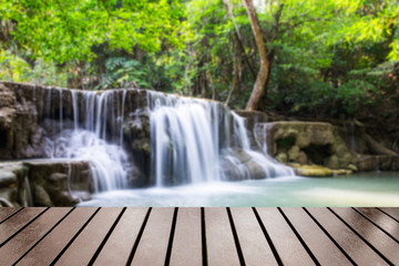 Wood table top on blurred waterfall tropical rain forest