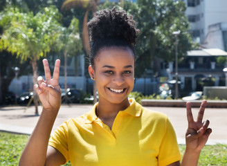 Beautiful woman with amazing hairstyle showing victory sign