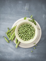 Ceramic bowl with fresh raw green peas, several pea pods and green bine on shabby grey wooden background.