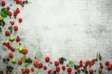 Different berries on the stone table.