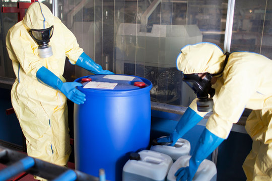 Workers in protective suits with toxic waste