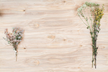 Dry flowers and herbs collage composition at wooden desk