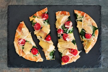 Flat bread pizza with melted mozzarella, tomatoes, spinach and artichokes, overhead view on slate
