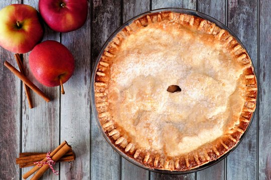 Delicious autumn apple pie, overhead table scene on a rustic wood background