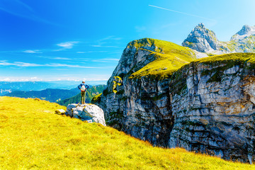 man standing in beautiful alpine mountain landscape on summer day.