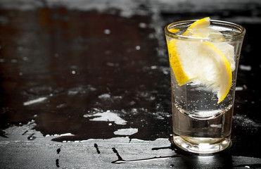 Glass with vodka and lemon.