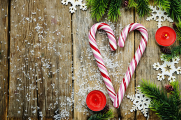 wood background with Christmas tree, candy and snowflakes