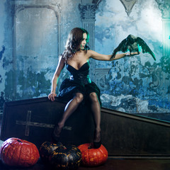 Young and sexy woman, image of witches in a cemetery sitting on lid coffin.