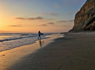 Surfer walking on the beach at sunset, Black's Beach, La Jolla, California, USA