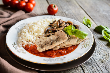 Fried pork cutlets with rice, tomato and mushrooms