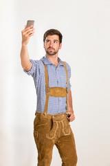 Junger Mann in Lederhose macht ein Selfie mit seinem Handy