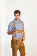 Junger Mann in Lederhose bedient sein Handy