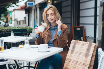 Beautiful blond woman sitting alone in cafeteria, smoking a cigarette and drinking coffee.