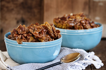 Hot autumn dessert pumpkin cobbler made with pumpkin spice and pecans against a dark rustic moody background.