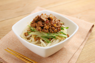 Udon noodle with minced beef and vegetables in white bowl on tab