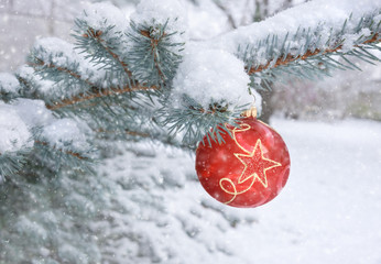 Red bauble on a Christmas tree under falling snow
