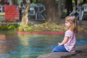 Kind sitzt alleine an einem See