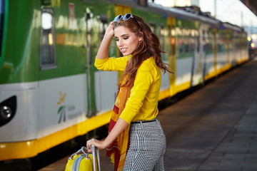 pretty adult woman with a suitcase near the train on the platfor