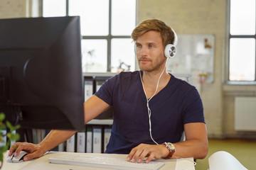 mann hört musik während der arbeit am pc