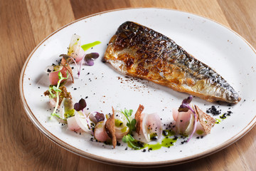 Fried mackerel with radish and shallots on white plate