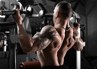 Athlete muscular bodybuilder training back on simulator in the gym