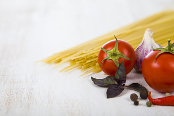 Raw pasta and spices on a wooden table