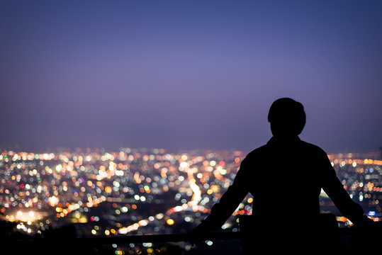 Silhouette of man stand looking above the city in the night