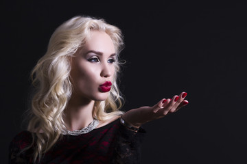 Beautiful blond woman blowing on his hand.