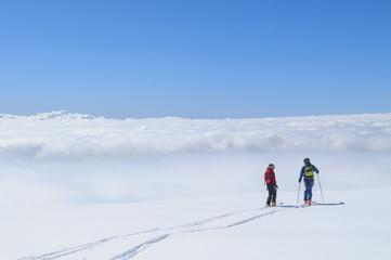 Zwei einsame Freeskier genießen die grenzenlose Freiheit über den Wolken