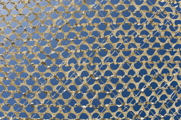 Detail of a beige camouflage grid paper, on the bottom blue sky