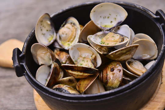 Garlic white wine clam in black pot on wooden tray in asian rest