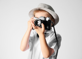 Little boy with vintage camera on grey background