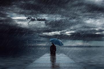A women sitting under the heaving rain