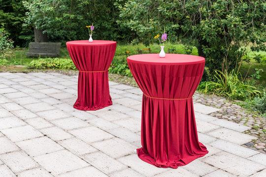 Weiße Vase auf einem rotem Tisch