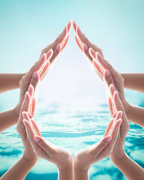 Saving water clean natural environment ocean campaign concept with collaborative woman's hands in droplet shape on blurred wavy clean water background: Love earth, save water conceptual idea