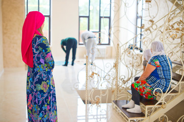 Men in muslim family pray together. Women are watching them behind