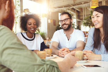 Friendship and communication concept. Four young people of diverse ethnicities or cultures dressed casually chatting at coffee shop, smiling and laughing, looking carefree, telling comic stories