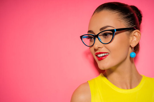 Close up colorful studio portrait of pretty young woman in glasses with red lipstick makeup.