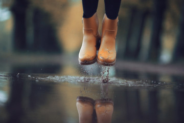 feet in rubber boots rain puddle city