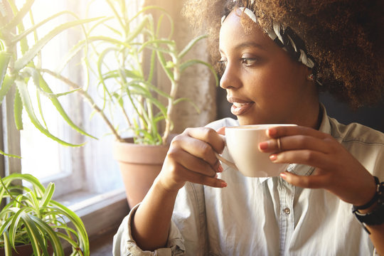 Young fashionable dark-skinned woman holding cup of hot drink, enjoying coffee or tea, trying to warm up after long walk, sitting at cafe near window and looking outside with pensive expression