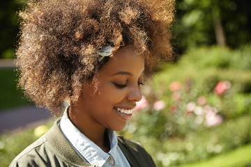 Dark-skinned student girl with Afro hairstyle in bandana resting in city park after lectures at university. Happy black woman with cheerful dreamy smile contemplating nature during walk on spring day