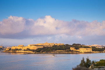 Manoel Island with Fort Manoel at sunrise with fishing boat and beautiful clouds