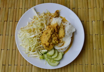 rice noodle with chicken and fish curry sauce on dish