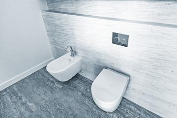 Two white closed toilet bowls.