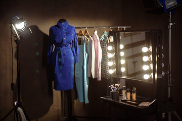 Stylish clothes and make-up products in dressing room