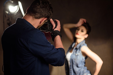 Man photographing woman in studio