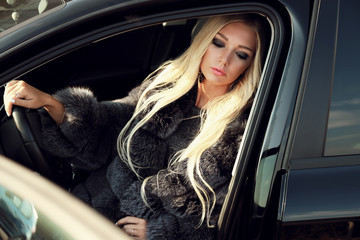 fashion outdoor photo of gorgeous sexy woman with long blond hair in casual clothes and fur posing beside luxurious car