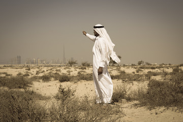 Arab man in national dress stands in the desert and looks at the