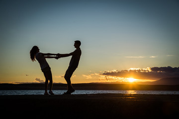 Couple playing, enjoying each other on the beach with a beautiful sunset in background