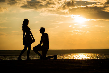 Romantic portrait of attractive couple in love playing on the beach at the sunset on tropic island. Against the backdrop of the sea and setting sun. Silhouette
